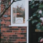 Photo of a modern house with a rainbow drawing in the window to illustrate a blog post about what COVID-19 has taught us about the benefit system