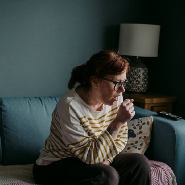 Image of a woman coughing on her couch to depict someone living in households hit by Coronavirus (COVID-19)
