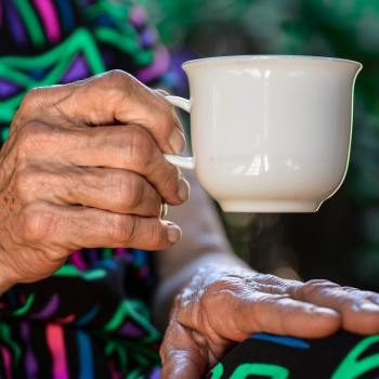 photo of older person's hands holding a tea cup to illustrate a blog post on the Health and Social Care Levy