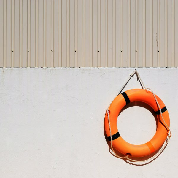Image of an orange life buoy against a light grey wall to illustrate the importance of the welfare state after Coronavirus
