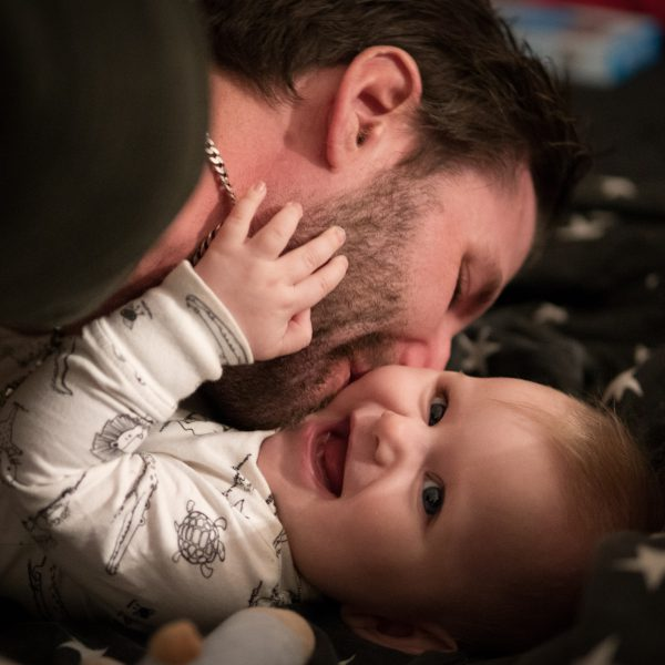 Man kissing laughing baby to illustrate importand of Healthy Start vouchers